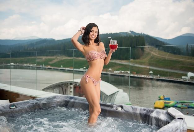 Frau im bikini, der draußen mit cocktail am jacuzzi steht
