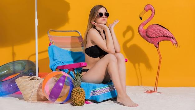 Frau im bikini, der im deckchair stillsteht
