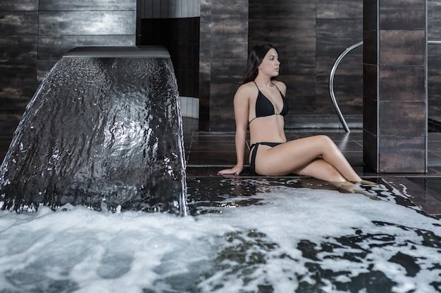 Frau im bikini, der im spa-pool kühlt