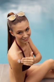 Frau im bikini, der lichtschutzlotion auf ihrem körper nahe poolside anwendet