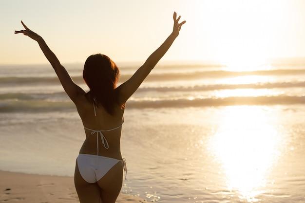 Frau im bikini, der mit den armen oben auf dem strand steht