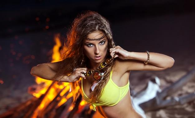 Frau im bikini, der nahe einem feuer aufwirft