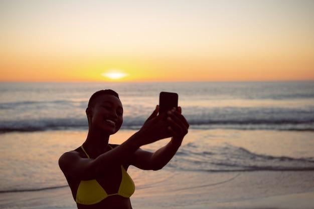 Frau im bikini, der selfie mit handy auf dem strand nimmt