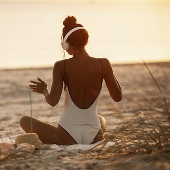 Frau im bikini, die musik mit kopfhörern auf natur genießt