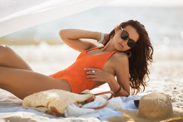 Frau im bikini, die während der sommerferien am meer bräunt