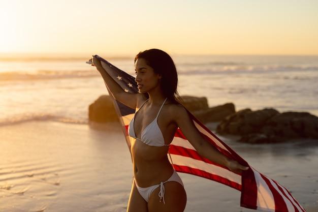 Frau im bikini hält eine amerikanische flagge am strand