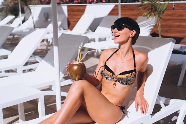 Frau im bikini kokosnussmilch durch das pool trinkend