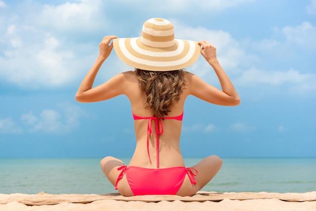 Frau im bikini mit dem sonnenhut, der am strand im sommer sitzt