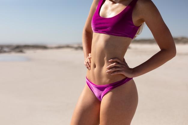 Frau im bikini mit den händen auf der hüfte, die am strand im sonnenschein steht