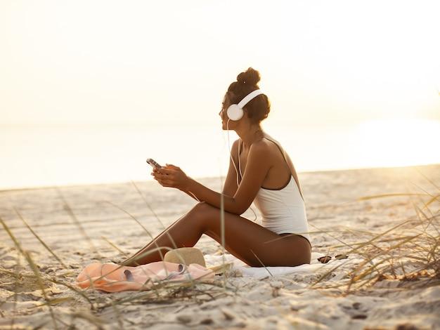 Frau im bikini mit einem smartphone und kopfhörern am strand