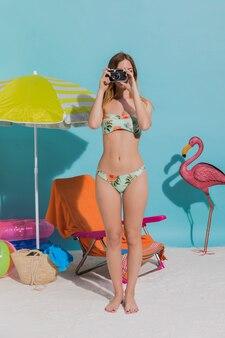Frau im bikini mit fotokamera