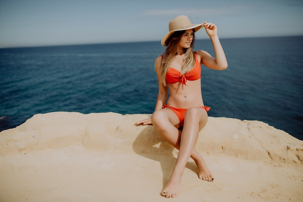 Frau im bikini sitzt am rande eines berges