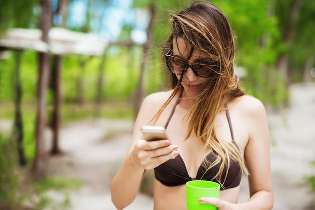 Frau im bikini sms-nachrichten trinken cocktail aus schickem glas