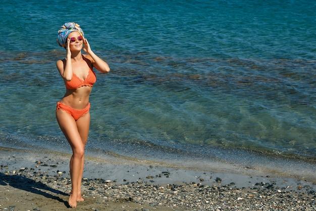 Frau im bikini und sonnenbrille am strand