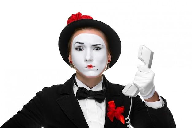 Frau im bild pantomime, der einen hörer hält.