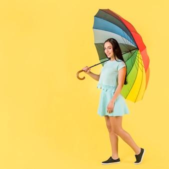 Frau im blau mit regenbogenregenschirm