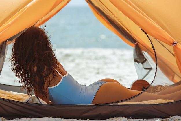 Frau im blauen badeanzug am strand unter einem orangefarbenen zelt