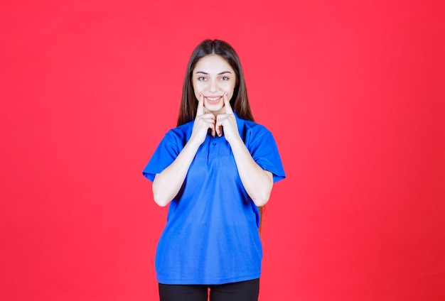 Frau im blauen hemd, die auf roter wand steht.