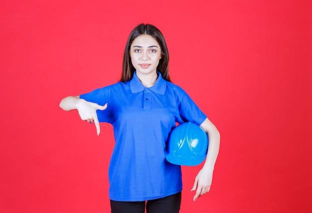 Frau im blauen hemd, die einen blauen helm hält und auf irgendwo herum zeigt.
