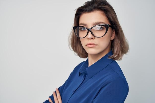 Frau im blauen hemd mit brille im eleganten stil selbstbewusstseinsstudio