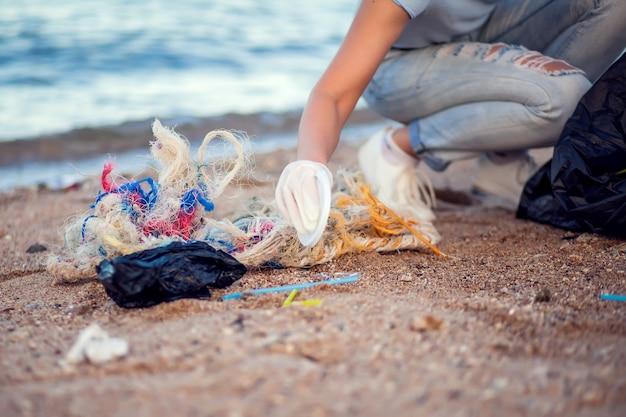Frau im blauen hemd mit weißen handschuhen und großem schwarzen paket, das müll am strand sammelt. umweltschutz- und planetenverschmutzungskonzept