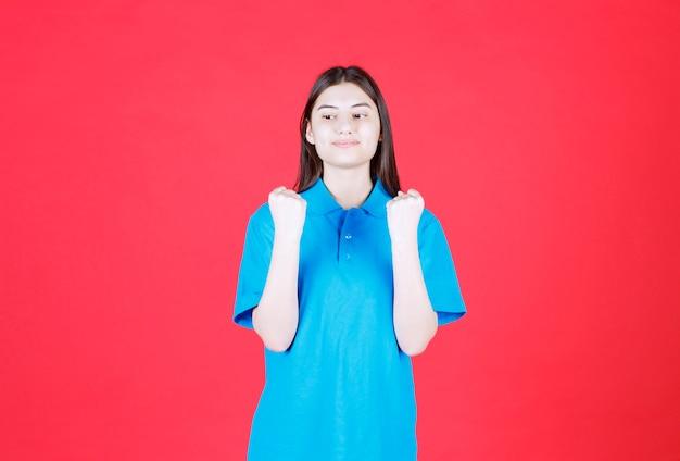 Frau im blauen hemd stehend und zeigt positives handzeichen.