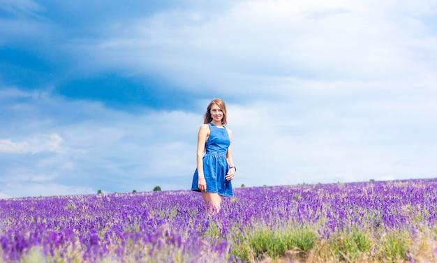 Frau im blauen kleid auf lavendelfeld bei bewölktem wetter.