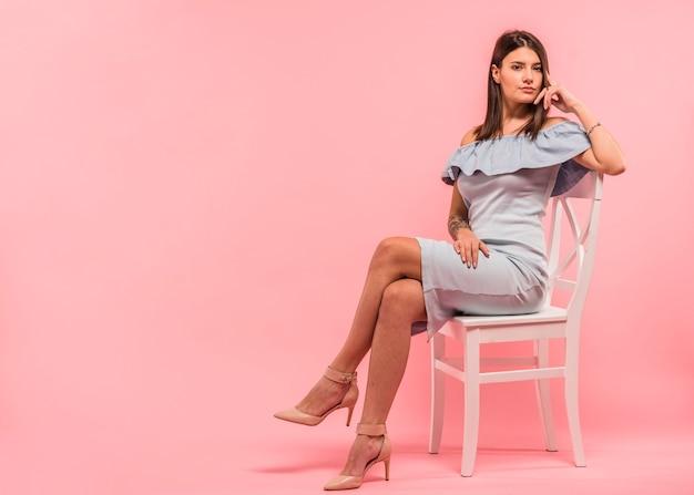Frau im blauen kleid, das auf stuhl sitzt