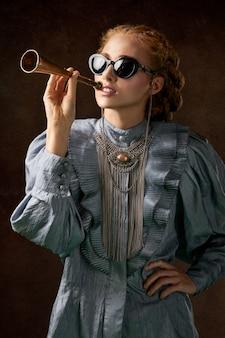 Frau im blauen kleid mit langen ärmeln, das trompete hält