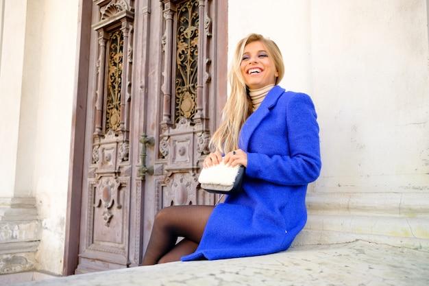 Frau im blauen mantel auf der straße
