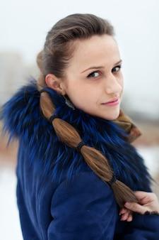 Frau im blauen mantel im winterlichen park