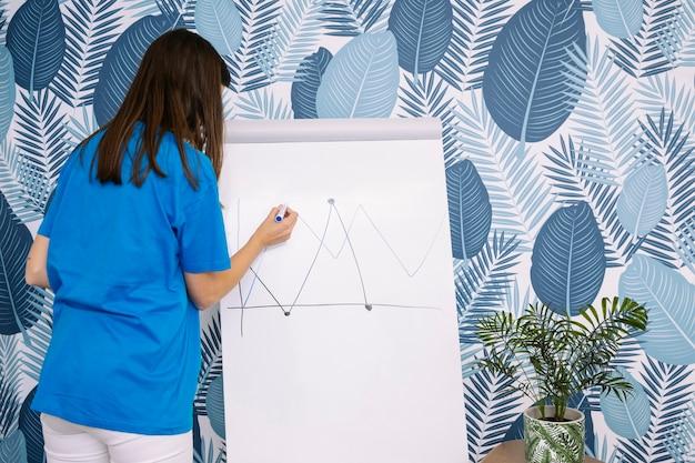 Frau im blauen t-shirt zeichnungsdiagramm mit markierung auf flipchart gegen tapete