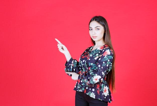 Frau im blumenhemd, das auf roter wand steht und linke seite zeigt.