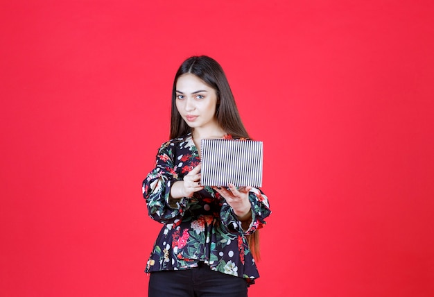 Frau im blumenhemd, das eine silberne geschenkbox hält.