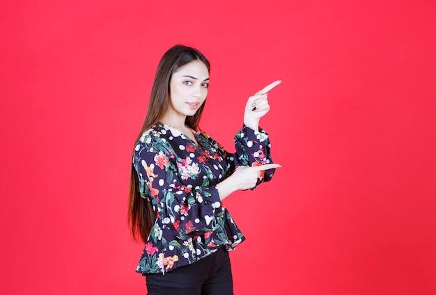 Frau im blumenhemd, die auf roter wand steht und nach rechts zeigt.