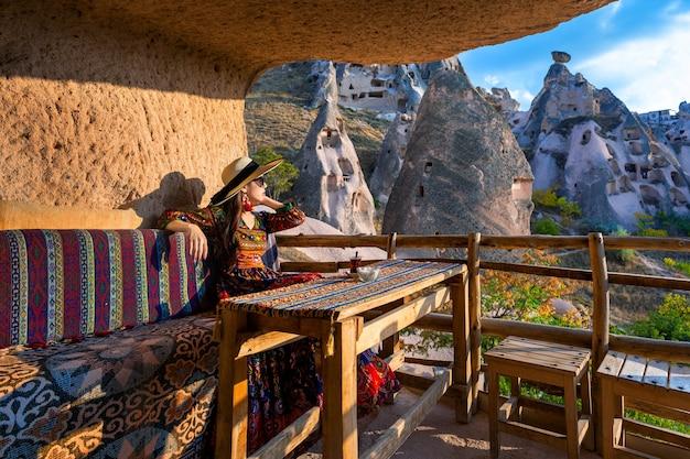 Frau im böhmischen kleid, das auf traditionellem höhlenhaus in kappadokien, türkei sitzt.