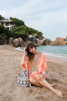 Frau im boho-sommerkleid, das auf sand nahe meer sitzt. tropische stimmung.