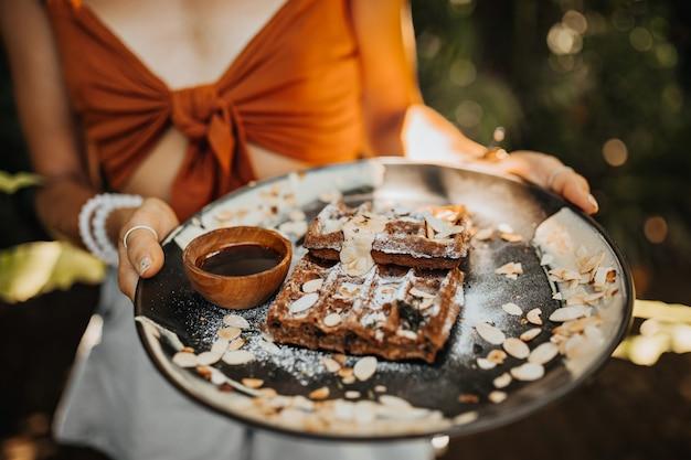 Frau im braunen bh hält teller mit waffeln, schokoladensauce und erdnüssen