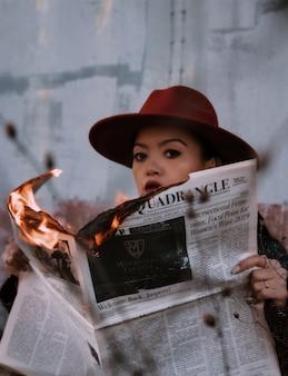 Frau im braunen hut, der brennende zeitung hält