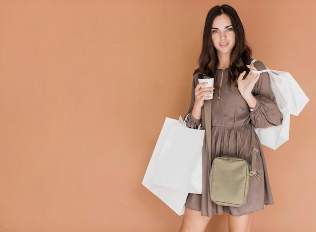 Frau im braunen kleid mit handtasche und kaffee