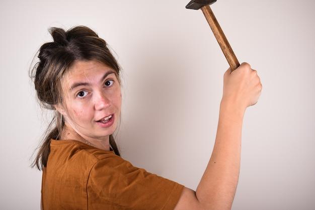 Frau im braunen t-shirt, hammer haltend, isoliert. hausrenovierungskonzept
