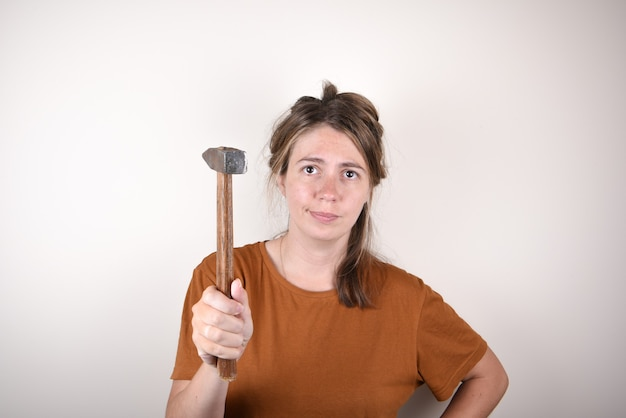 Frau im braunen t-shirt, hammer haltend, kamera betrachtend, lokalisiert auf weißem hintergrund
