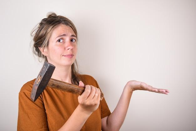 Frau im braunen t-shirt, hammer haltend, kamera betrachtend, lokalisiert auf weißer wand. hausrenovierungskonzept