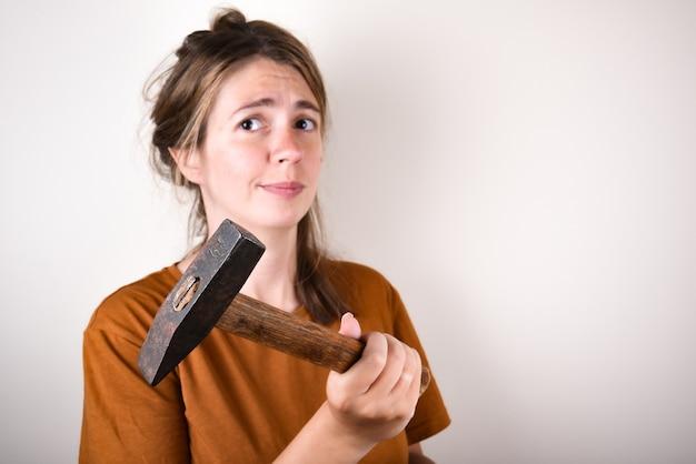 Frau im braunen t-shirt, hammer haltend