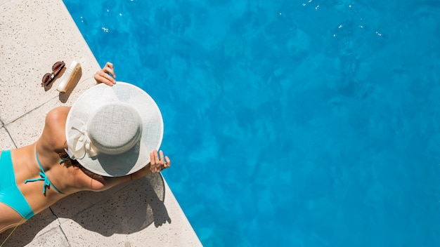 Frau im breitkrempigen hut, der auf poolgrenze liegt