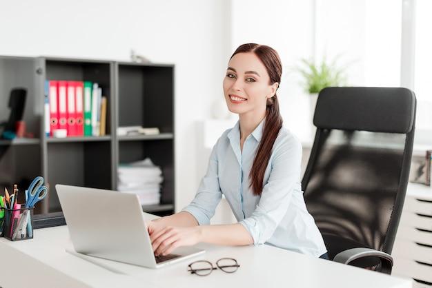 Frau im büro am schreibtisch mit dem laptoplächeln