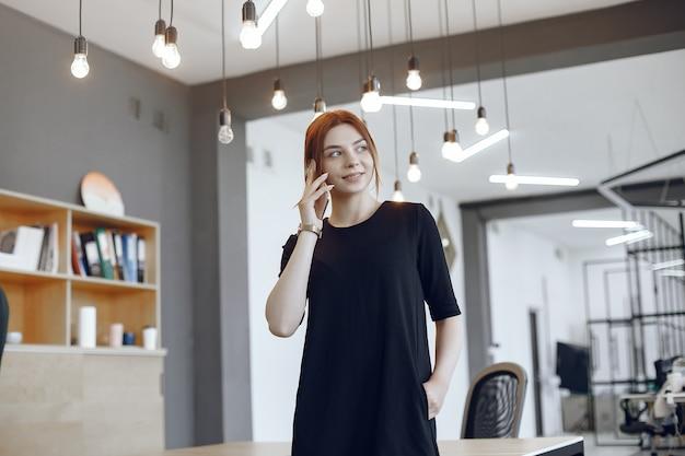 Frau im büro. arbeiter tallking. dame in einem schwarzen kleid.