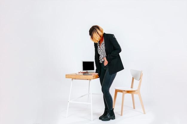 Frau im büro, das magenschmerzen hat