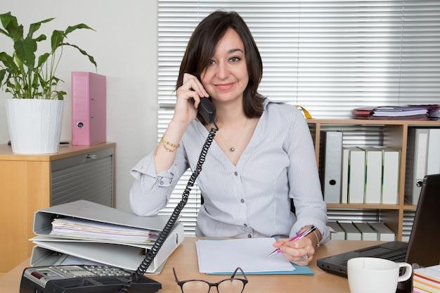 Frau im büro, die auf handy spricht