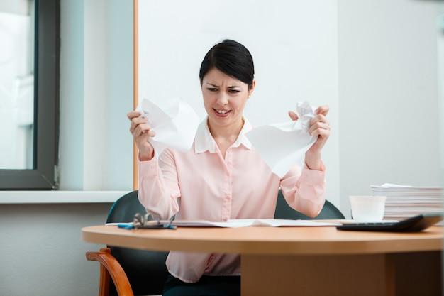 Frau im büro mit zerknittertem papier. konzept des bürolebens.